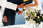 Happy groom and bride exchanging rings at aisle during ceremony with sea in background poster