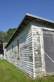 A farm chicken house once used for raising poultry and eggs is in disuse and has peeling paint. poster