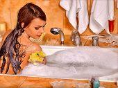 Young woman take bubble  bath. Woman washing her shoulder by yellow sponge. poster