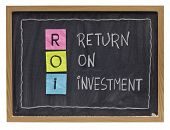 ROI - return on investment acronym explained with color sticky notes and white chalk handwriting on blackboard poster