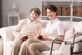 Happy young female carer and senior woman spending time together poster