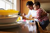 Son Helping Mother To Wash Dishes In Kitchen Sink poster