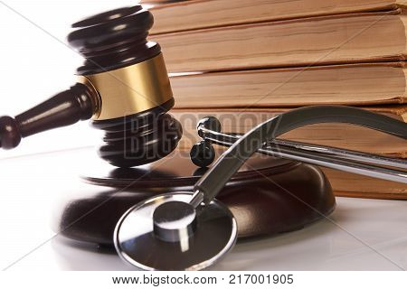 Judge gavel and medical stethoscope near law textbook in library archive study room, close-up. Forensic medicine investigation or malpractice justice concept