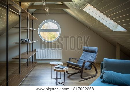 Modern attic with light walls and a parquet on the floor. There are round and rectangle windows, wooden shelves, small tables, blue armchair and a sofa with pillows, hanging lamps, radiator.