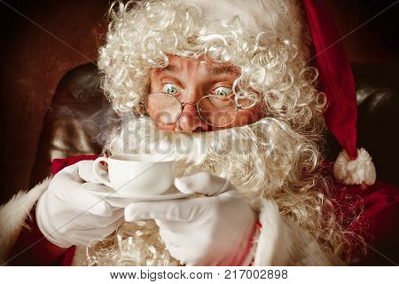 Portrait of Man in Santa Claus Costume - with a Luxurious White Beard, Santa's Hat and a Red Costume at red studio background sitting in a chair with cup of coffee