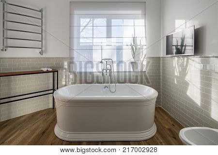 White bath with a chrome shower in the modern bathroom with light walls with tiles. There is a window with curtain, wooden rack with towels, heated towel rail, TV on the wall, toilet. Horizontal.