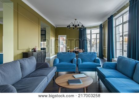 Contemporary interior with colorful walls and large windows with blue curtains. There are blue armchairs and sofas, wooden tables, dark locker with bottles, chairs, fancy hanging black lamp. Indoors.