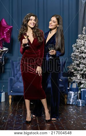 Delightful smiling girls holding drinks in the decorated studio with a Christmas tree and gift boxes. They dressed in velvet red dress with black shoes and velvet blue pantsuit with dark sandals.