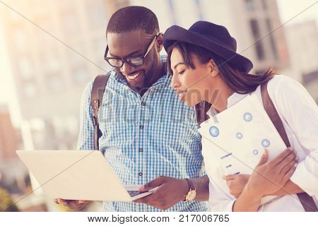 Modern students. Attractive smart young woman holding her documents and looking at the netbook screen while walking together with her friend