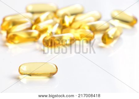 Yellow color soft gelatin capsule on white background (Concept of medicine drug nutrition supplement)