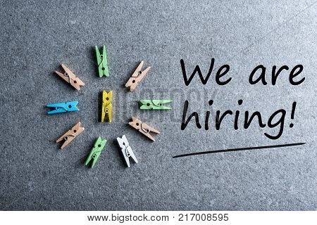 WE ARE HIRING - job recruiting advertisement represented by texts on wooden plaque. Announcement of hiring position to be recruited and filled.