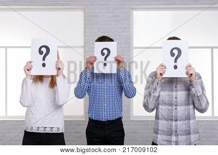 Two guys and a girl stand side by side close their faces with sheets with question marks. The guy in the blue shirt is standing in the middle
