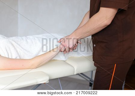 Stately male therapist and massage therapist makes massage movements with hands, relieves fatigue and tension from girl's girlfriend's brushes, who came to reception and lies on couch up to half covered with terry towel in light cosmetology salon