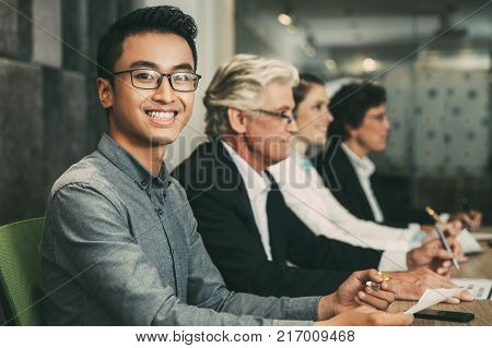 Smiling young Asian businessman wearing glasses and shirt sitting at conference table in boardroom with his colleagues, holding pen and looking at camera. Business people at workshop or seminar