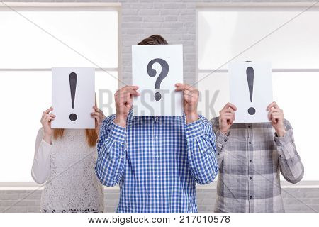 Three people covered their faces with signs. In the middle of the question mark, on the sides are exclamation marks