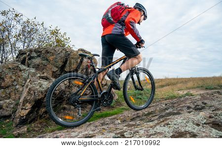 Cyclist in Red Riding the Mountain Bike up the Autumn Rocky Trail. Extreme Sport and Enduro Biking Concept.