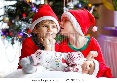 One week old newborn baby girl and two siblings kid boys in Santa Claus hats near Christmas tree with colorful garland lights on background. Close-up of three children, happy family celebrating Xmas