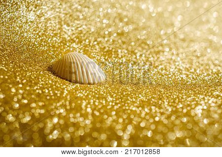 A scene of sea shell on artificial glittering sand in gold color represents the concept hope, wishing and wealthy.