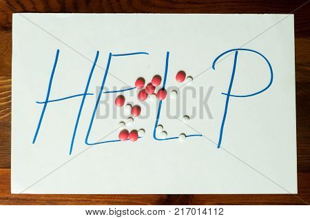 Help sign letters written on paper with strong pain killer pills or tablets addiction or suicidal concept