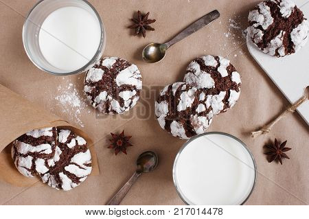 Chocolate crinkle cookies and glasses of milk on the table covered with craft paper poster