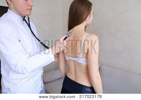 Professional male doctor advises and conducts general examination, applies stethoscope to back and listens to deviations of cute girl who came to reception and complains about health. Guy physician with European-style with short haircut dressed in white m