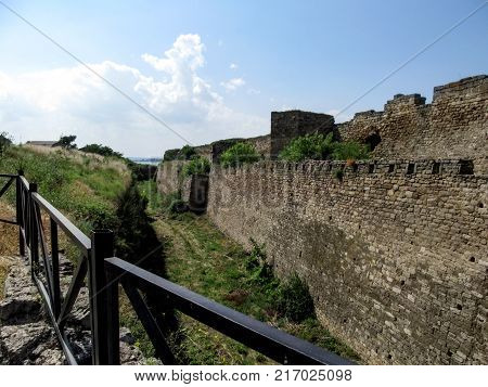 The moat near the stone wall of the Akkerman fortress in Bilhorod-Dnistrovskyi (Ukraine). A dilapidated ancient wall a trench overgrown with grass blue sky and sea away on the horizon