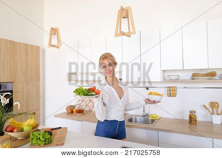 Slender girl housewife poses and smiles, enjoys aroma of fresh cooked dinner and holds flat plate with tomatoes, cucumbers and lettuce leaves, deep plate with potato chips and tastes food while standing at kitchen table with electric stove in stylish ligh