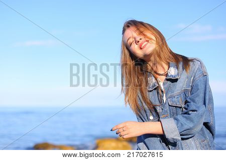 Beautiful young woman with small smile on lips looks at camera and smiles with broad smile, looks at camera and plays with eyes and eyes. young European-looking woman with blond mid-length hair dressed in blue denim jacket