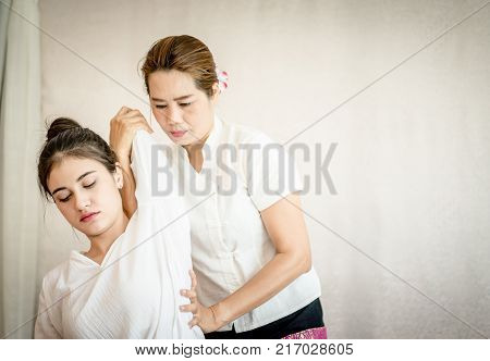 Woman is getting arm massage stretch in Thai massage