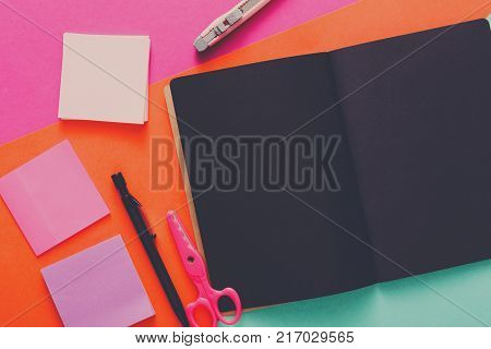 Stationery at modern creative work space. Stylish open notepad with black pages, pink scissors, office knife, marker and memo notes on abstract multicolored background, top view, copy space
