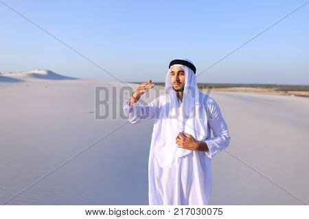 Serious young Arab man peers into distance and tries to see caravan of camels walking, puts hand to forehead defensively against bright sun in hot wide desert with white sand on clear summer day. Swarthy Muslim with short dark hair dressed in kandura, lon