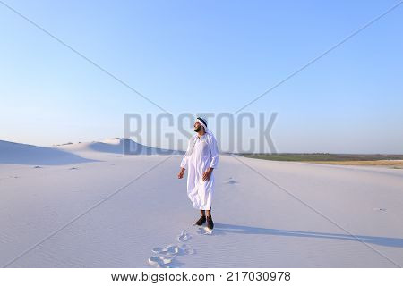 Successful Muslim tourist guy smiles broadly and spreads hands to sides and whirls around, laughs and smiles in desert on clear warm day. Swarthy, handsome Muslim with short dark hair dressed in kandura