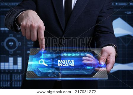 Business Technology Internet and network concept. Young businessman working on a virtual screen of the future and sees the inscription: Passive income