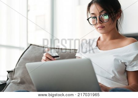 Image of serious young woman sitting on sofa at home. Looking aside holding debit card using laptop computer.