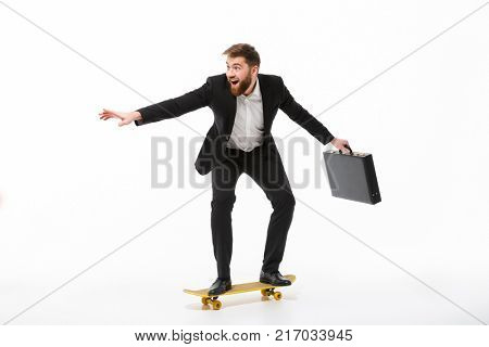 Full length image of Playful bearded business man with briefcase riding on skateboard over white background
