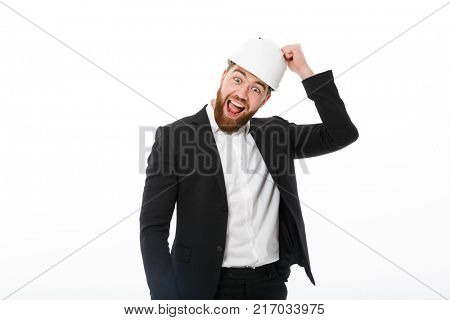 Happy bearded business man in protective helmet knocks on it and looking at the camera over white background