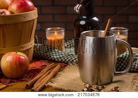 Apple cider in a stainless steel mug with a cinnamon stick