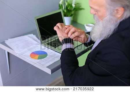 Senior publishes latest phrases on computer and introduces amendments to business plan and completes workflow, checks notifications of calls on iWatch watches sitting at table in modern office. Elderly man with long gray beard of European appearance dress