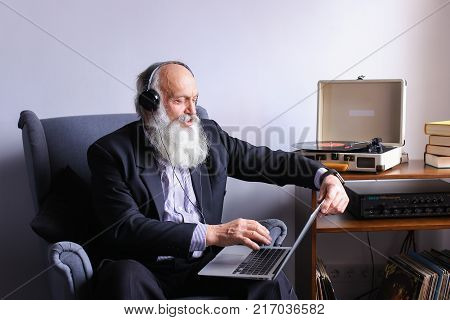Male golden-ager, having closed his eyes, enjoys familiar melodies and quietly sings music holding on to headphones and sits with computer on his lap in gray soft armchair next to pedestal with books, musical plates and pinophone in bright room