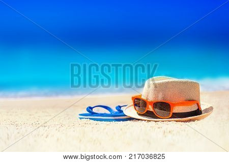 Flip-flops beach hat sun glasses on the sand. Summer vacation concept. Summer fun time and accessories on tropical beach