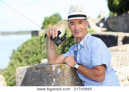 Older male tourist with binoculars leaning on the citadel walls at Blaye in SW France