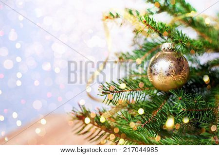 Fir-tree spruce with Christmas golden decor balls. Holiday background. Copy space.