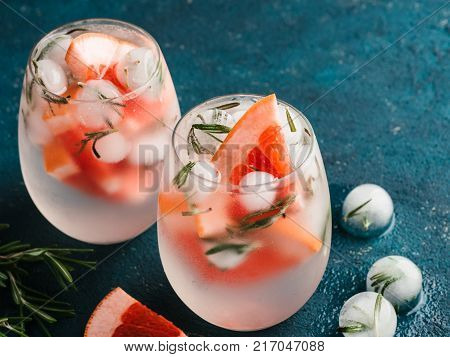 infused detox water or alcoholic or non-alcoholic cocktail with grapefruit and rosemary ice in glass on green cement background. healthy eating or holyday drink concept, copy space for text.