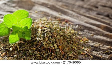 Pile of dry origanum with a fresh one. Closeup view and space for text.