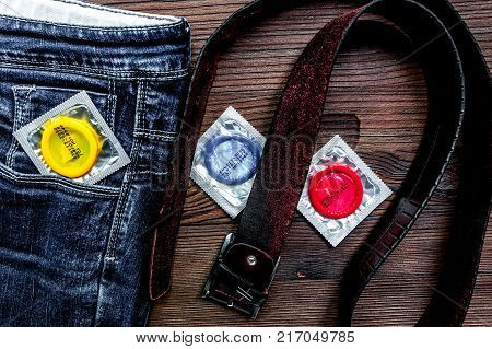 safe sex with condom contraception in jeans pocket on wooden desk background top view