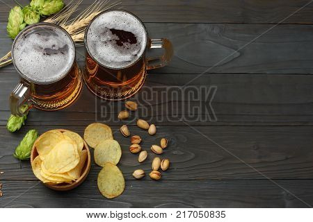 Glass Beer With Hop Cones, Pistachio And Wheat Ears On Dark Wooden Background. Beer Brewery Concept.