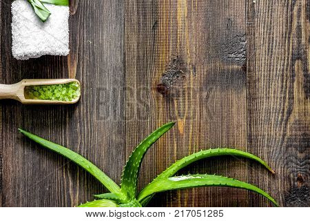 Organic aloe vera cosmetics. Aloe vera leafs and spa salt on wooden table background top view.