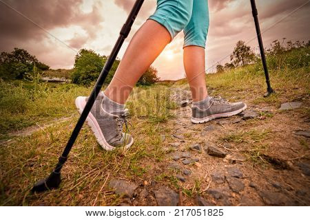 Woman hiking with sticks outdoor Active and healthy lifestyle concept.