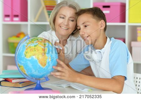 granny with her grandson doing homework at home