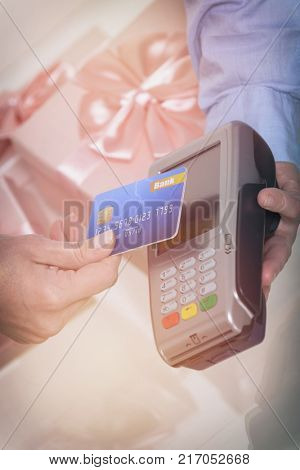Hand holding contactless credit or debit card over wireless payment terminal at shop with gifts in the background